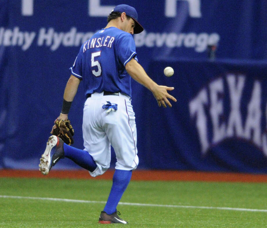 Texas second baseman Ian Kinsler chases down a ball that went for a base hit during Big League Weekend action against San Diego at the Alamodome on Friday, March 29, 2013. Photo: Billy Calzada, Express-News / San Antonio Express-News