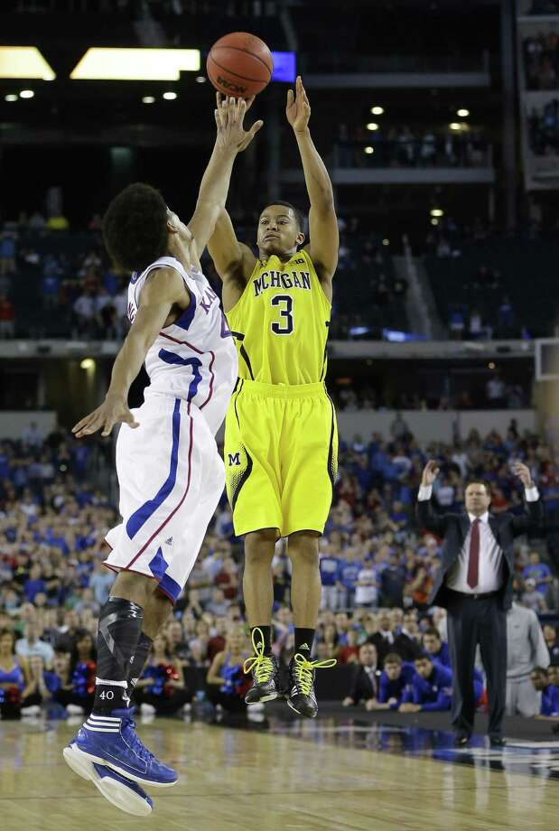 Michigan's Trey Burke fires up the game-tying 3-point shot over Kansas' Kevin Young with four seconds left to force overtime as Jayhawks coach Bill Self reacts in the background. Photo: David J. Phillip / Associated Press