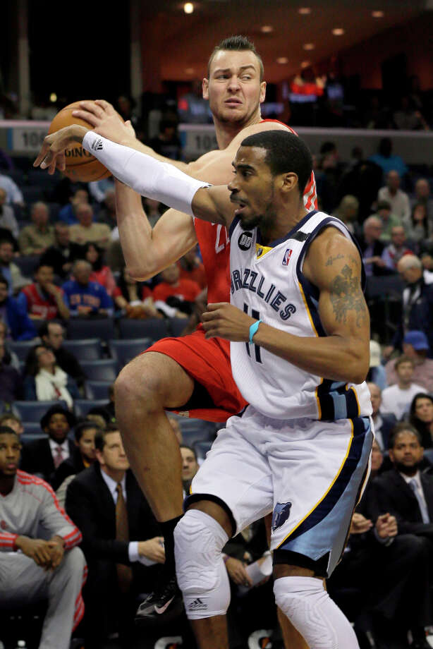 Donatas Motiejunas of the Rockets looks to pass against Mike Conley of the Grizzlies. Photo: Danny Johnston