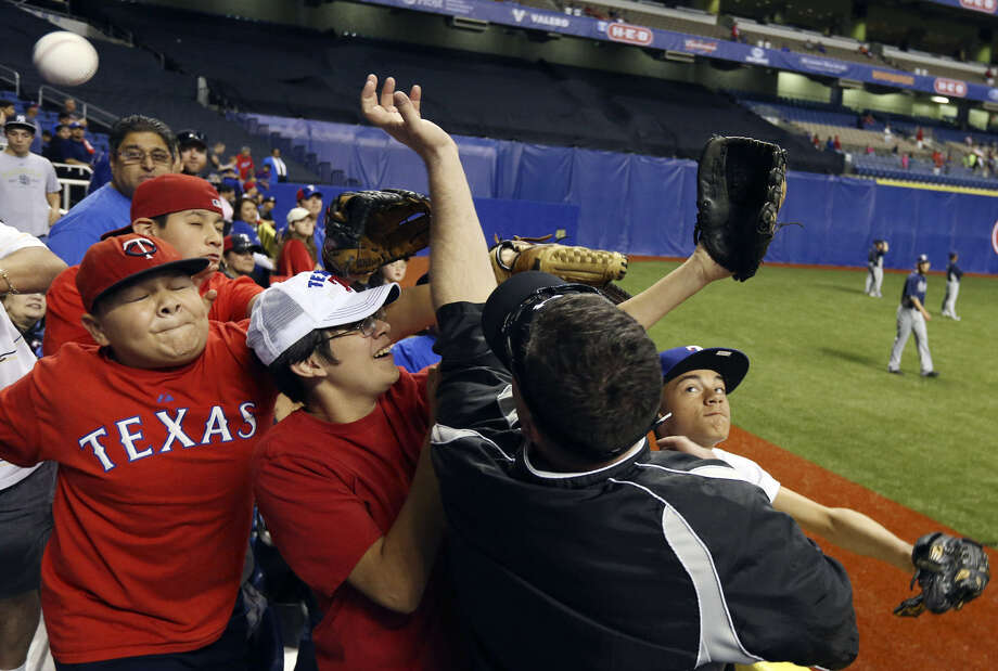 In photo above, fans grab for a ball during batting practice before the Texas Rangers-San Diego Padres game in the Alamodome. Photo: Edward A. Ornelas / San Antonio Express-News