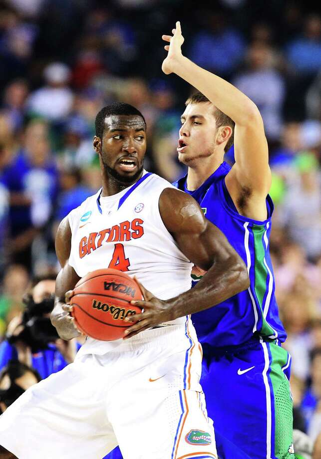 Florida's Patric Young (left) looks for an opening against Florida Gulf Coast's Chase Fieler in the first half of Friday's late game at Cowboys Stadium. Photo: Ronald Martinez / Getty Images
