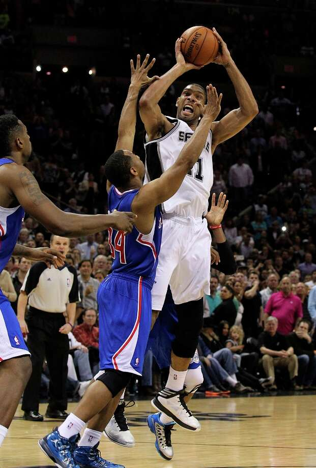 The Spurs' Tim Duncan (21) hits the winning shot against Los Angeles Clippers' Willie Green (34) late in the fourth quarter at the AT&T Center on Friday, Mar. 29, 2013. Spurs won 104-102. Photo: Kin Man Hui, San Antonio Express-News / © 2012 San Antonio Express-News
