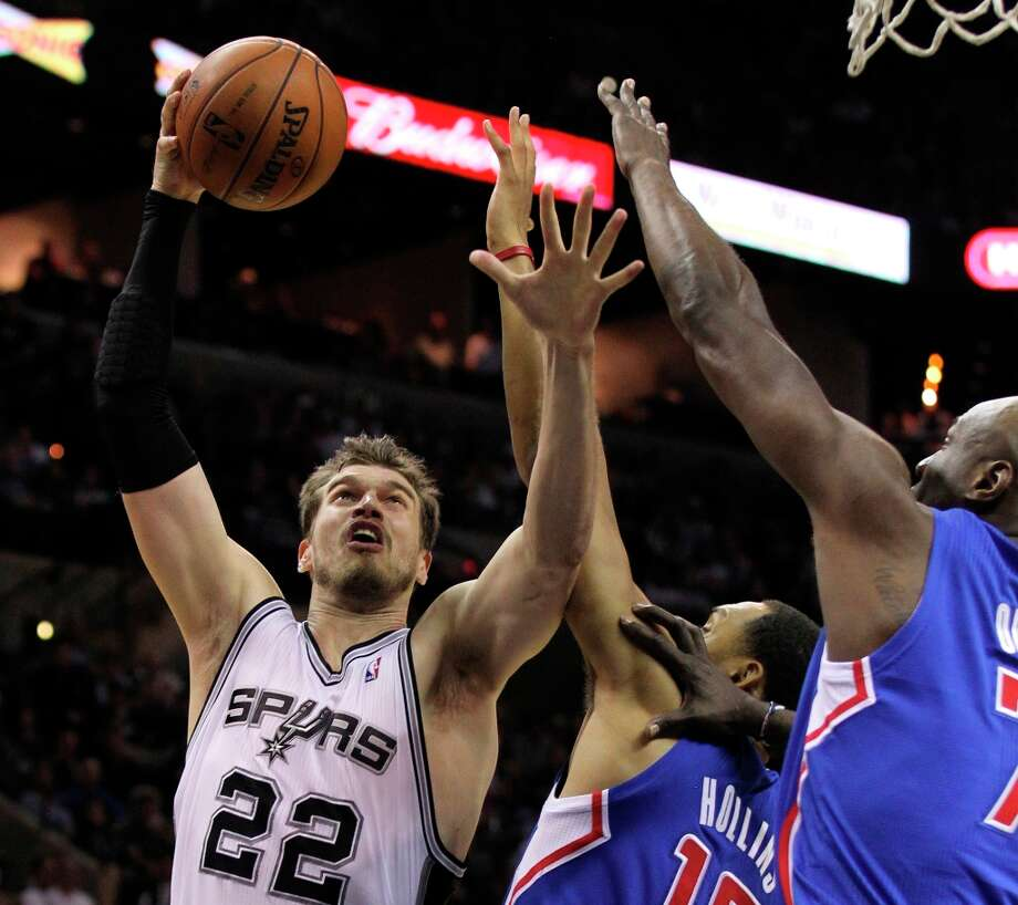 The Spurs' Tiago Splitter (22) attempts a shot against Los Angeles Clippers' Ryan Hollins (15) and Lamar Odom (07) in the second half at the AT&T Center on Friday, Mar. 29, 2013. The Spurs defeated the Clippers, 104-102. Photo: Kin Man Hui, San Antonio Express-News / © 2012 San Antonio Express-News