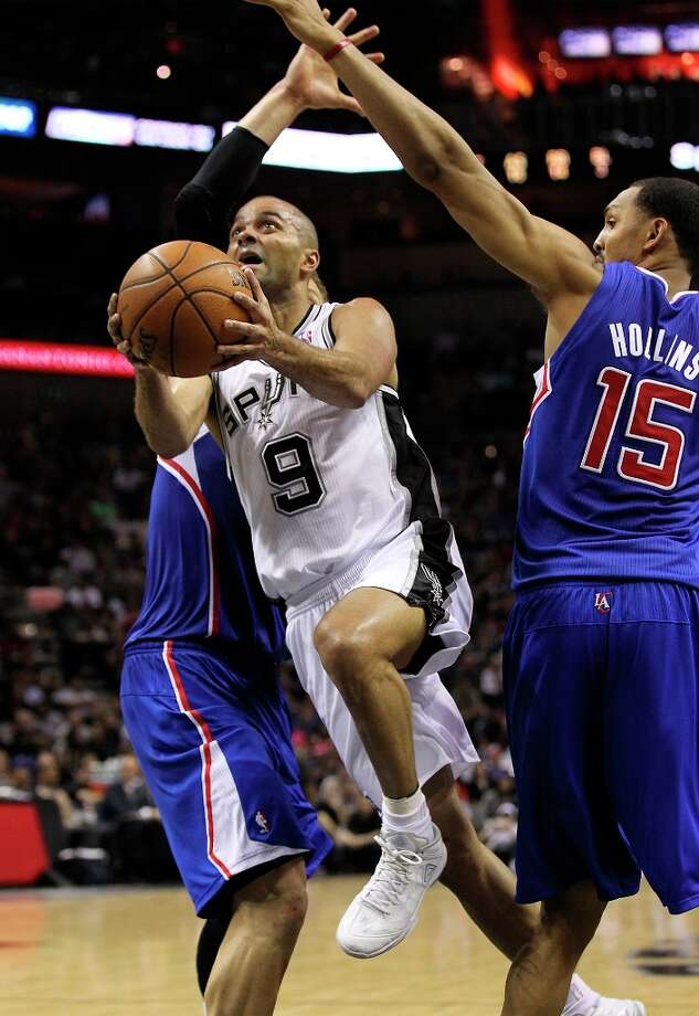 The Spurs' Tony Parker (9) drives past Los Angeles Clippers'  Ryan Hollins (15) in the second quarter at the AT&T Center on Friday, Mar. 29, 2013. Photo: Kin Man Hui, San Antonio Express-News / © 2012 San Antonio Express-News