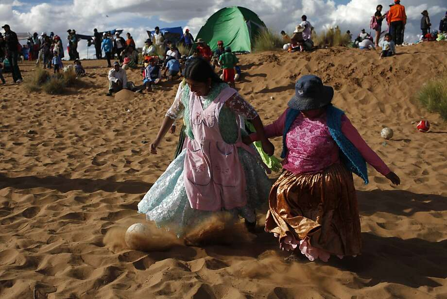 Two Aymara women fight for the ball in a pick-up game of soccer during Holy Week celebrations in Arenal de Cochiraya, on the outskirts of Oruro, Bolivia, Friday, March 29, 2013.  More than 150 Bolivian artists gathered for the annual Good Friday event in the highland region, building sand sculptures based on the parables of Jesus. Christians all over the world attend ceremonies and events that mark the day Jesus Christ was crucified, commonly known as Good Friday. (AP Photo/Juan Karita) Photo: Juan Karita, Associated Press