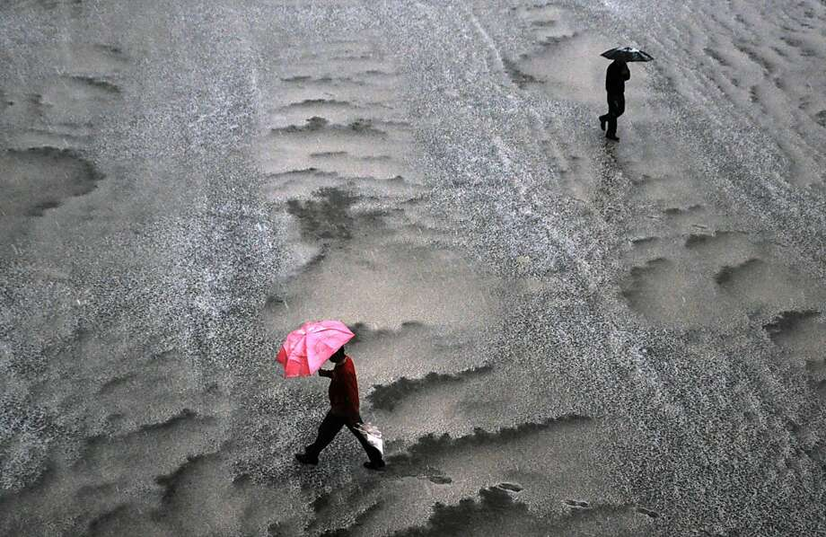 TOPSHOTS Indian pedestrians walk during a heavy hailstorm in the northern hill town of Shimla on March 29, 2013. A severe thunderstorm accompanied by heavy showers lashed Shimla and its adjoining hills while higher reaches received fresh snowfall.  AFP PHOTO/ STRSTRDEL/AFP/Getty Images Photo: Strdl, AFP/Getty Images