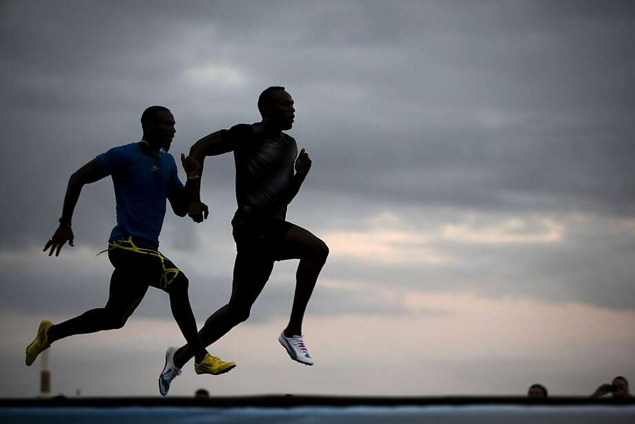 "Jamaican Olympic gold medalist Usain Bolt, right, runs with Antigua and Barbuda sprinter Daniel Bailey during a training session of the ""Mano a Mano"" challenge at Copacabana beach in Rio de Janeiro, Brazil, Friday, March 29, 2013. Bolt will compete Sunday on a track specially built at the famous beach, challenging Bailey, Ecuador's Alex Quinones and a Brazilian athlete from a local qualifier. (AP Photo/Felipe Dana) Photo: Felipe Dana, Associated Press"