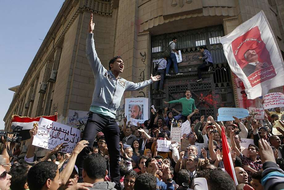 "Egyptian protesters chant slogans against Islamist President Mohammed Morsi slogans during a protest in front of the prosecutor general's office in Cairo, Egypt, Friday, March 29, 2013. Hundreds of activists demonstrated to show solidarity with political activists charged by the prosecutor general with inciting violence during last week's clashes near the Muslim Brotherhood's Cairo headquarters. Arabic banner at left reads, ""none can threaten us,"" and at center, ""freedom for activist Hassan Mustafa.""(AP Photo/Amr Nabil) Photo: Amr Nabil, Associated Press"