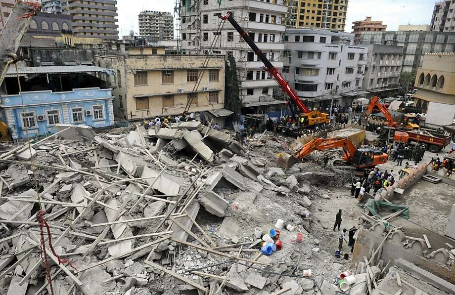 Rescuers using mechanical diggers remove rubble from the site of a collapsed building in downtown Dar es Salaam, Tanzania Friday, March 29, 2013. A Tanzanian police official says the multi-storey building was in the final stages of its construction and most of the people caught up in the collapse were passing by. (AP Photo/Khalfan Said) Photo: Khalfan Said, Associated Press