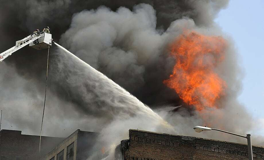 Firefighters battle a fire in a vacant building, Friday, March 29, 2013, in Birmingham, Ala.  A wall of a vacant office building in downtown Birmingham has collapsed after a fire tore through and sent plumes of black smoke drifting across the city's skyline.  (AP Photo/AL.com, Joe Songer) MAGS OUT Photo: Joe Songer, Associated Press