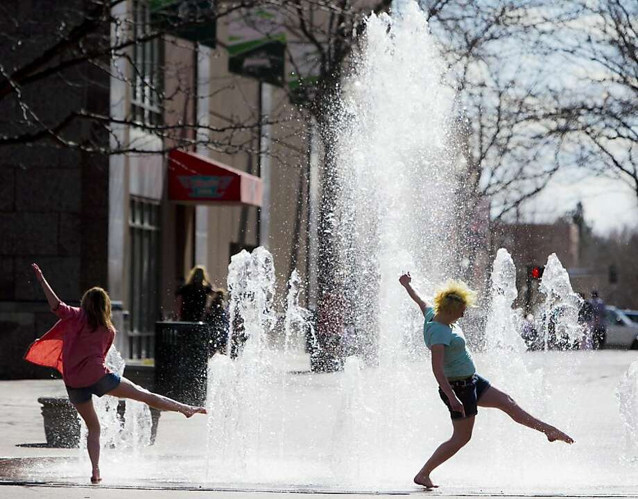 Kiri Albrecht, 18, right, and Annie Nelsen, 20, splash through The Grove fountain in downtown Boise, Idaho, on Friday, March 29, 2013. Temperatures reached into the high 60s Friday and are expected to warm into the low 70s this weekend. (Darin Oswald/Idaho Statesman/MCT) Photo: Darin Oswald, McClatchy-Tribune News Service