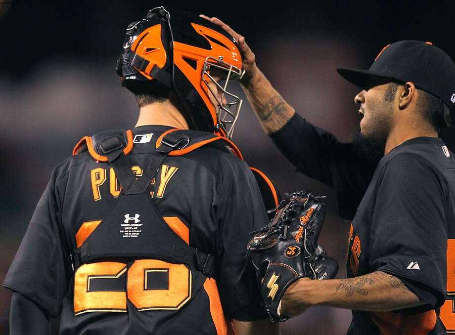 San Francisco Giants' catcher Buster Posey is greeted by pitcher Sergio Romo after the Giants defeated the Oakland Athletics in their exhibition spring training baseball game Friday, March 29, 2013 in San Francisco Calif. Photo: Lance Iversen, The Chronicle