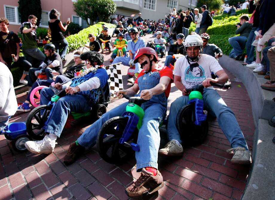 Spectators watch approximately two hundred drivers speed and crash down Lombard Street during the seventh annual Bring Your Own Big Wheel on April 8, 2007, in San Francisco. Photo: Lacy Atkins, Sfc / chronicle