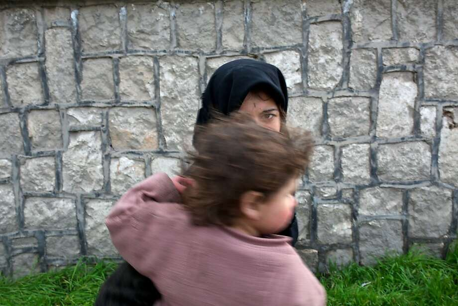 A woman begging for money carries a child in Aleppo, Syria Photo: Phillip Robertson