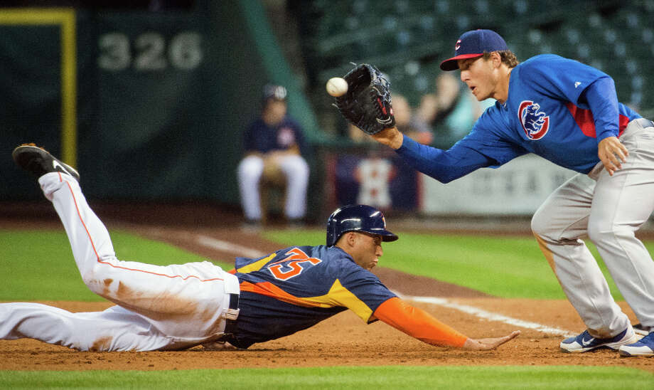 Astros outfield prospect George Springer dives back to first ahead of the tag from Cubs first baseman Anthony Rizzo. Photo: Smiley N. Pool, Houston Chronicle / © 2013  Smiley N. Pool