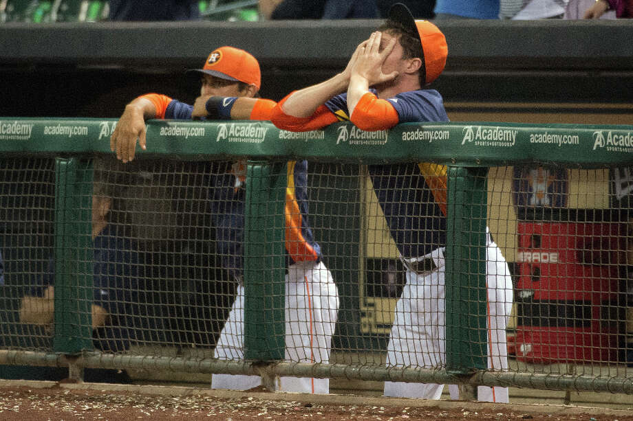Astros pitcher Lucas Harrell, right, covers his face as the game goes into extra innings.  The contest ended tied 6-6 after three hours and 49 minutes. Photo: Smiley N. Pool, Houston Chronicle / © 2013  Smiley N. Pool