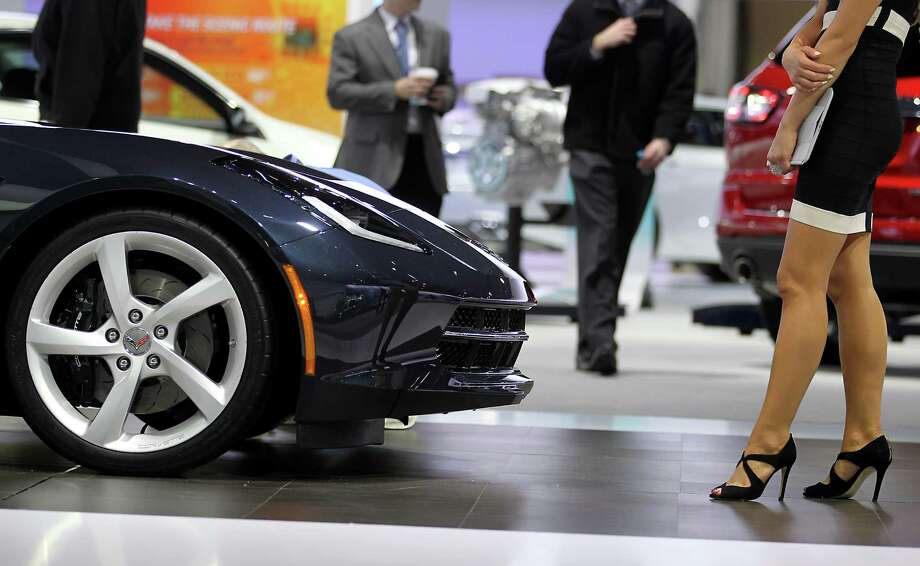 A model stands next to the 2014 Chevrolet Corvette. Photo: Jin Lee, Bloomberg / © 2013 Bloomberg Finance LP