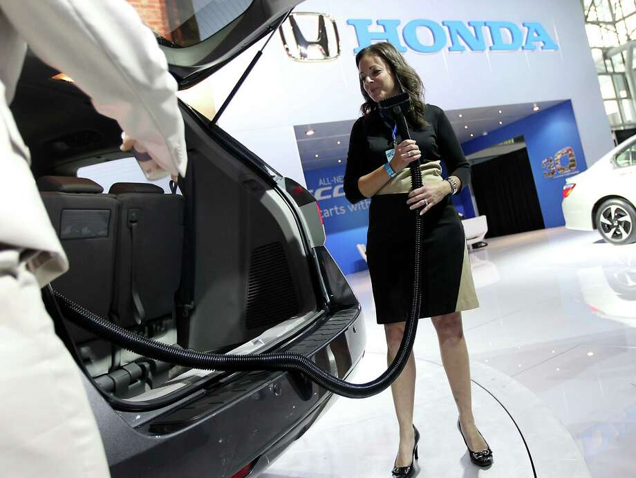 A Honda Motor Co. representative demonstrates the vacuum cleaner that comes with the 2014 Odyssey minivan during the 2013 New York International Auto Show in New York. Photo: Jin Lee, Bloomberg / © 2013 Bloomberg Finance LP