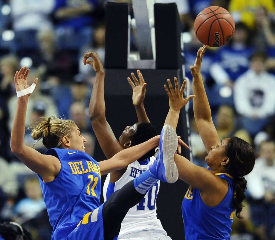 Delaware's Elena Delle Donne, left, blocks a shot by Kentucky's Brittany Henderson, center, as Delaware's Jaquetta May, right, defends during the first half of a regional semifinal in the NCAA college basketball tournament in Bridgeport, Conn., Saturday, March 30, 2013. (AP Photo/Jessica Hill)