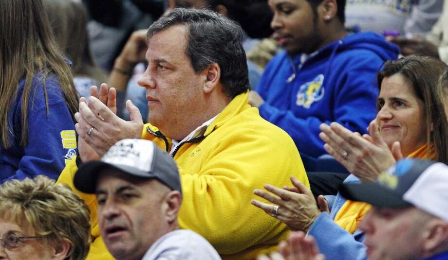 New Jersey Gov. Chris Christie applauds during the first half of a regional semifinal between Delaware and Kentucky in the NCAA college basketball tournament in Bridgeport, Conn., Saturday, March 30, 2013. (AP Photo/Charles Krupa)