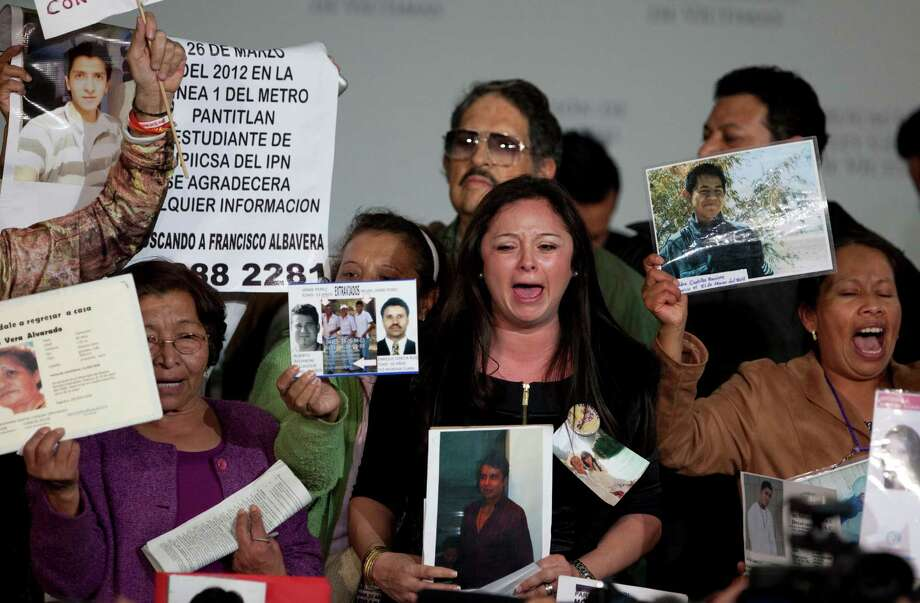 Residents of Mexico City hold up images of alleged crime victims as they demonstrate after President Enrique Peña Nieto enacted a law requiring local and federal authorities to compensate victims by covering their health and psychiatric care costs and mandating the creation of a relief fund and national registry of victims of crime. Photo: Eduardo Verdugo, STF / AP