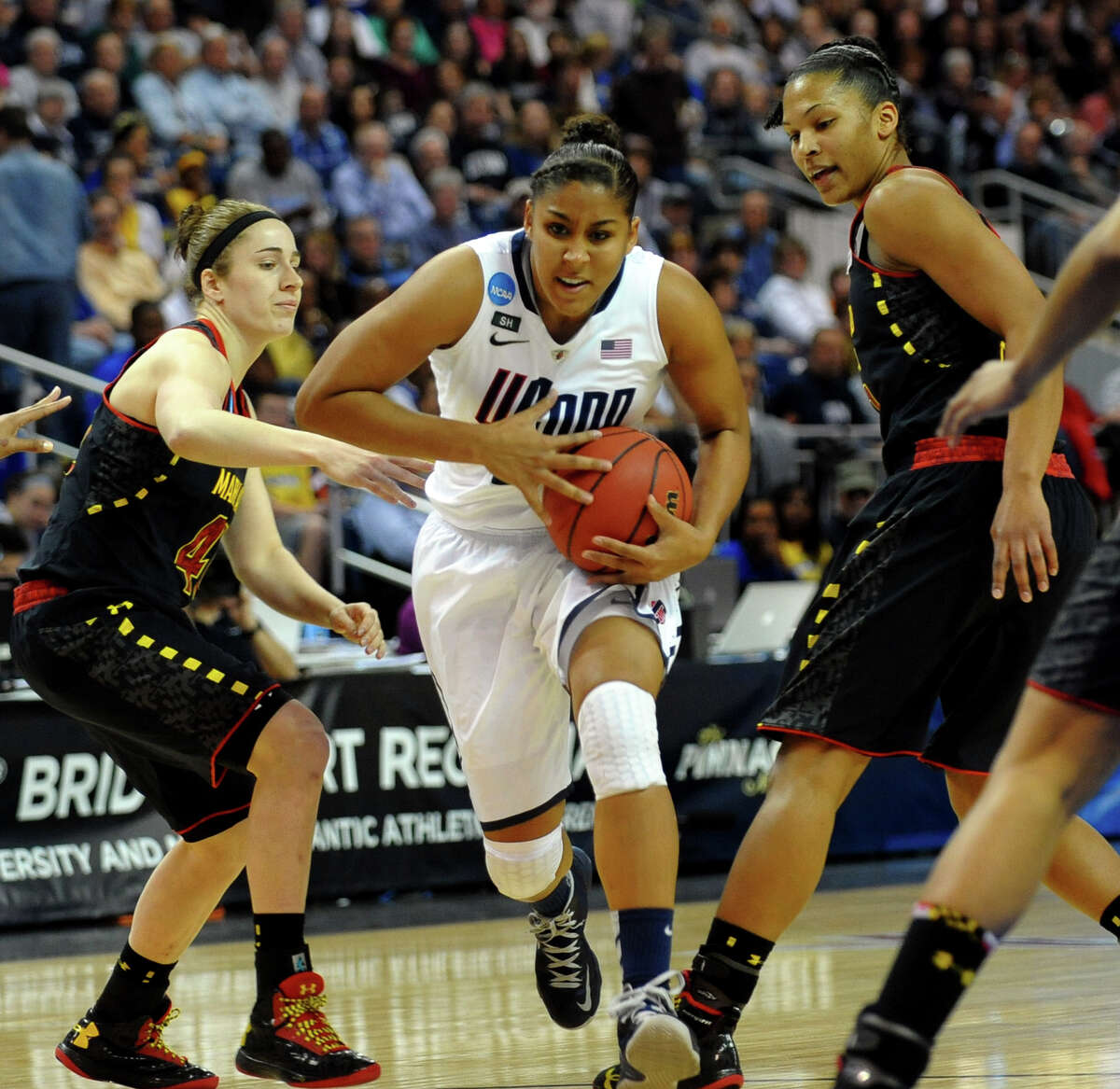 UConn's Kaleena Mosqueda-Lewis passes through two University of Maryland defenders, during the women's NCAA Tournament Regional Semifinals at the Webster Bank Arena in Bridgeport, Conn. on Saturday March 30, 2013.