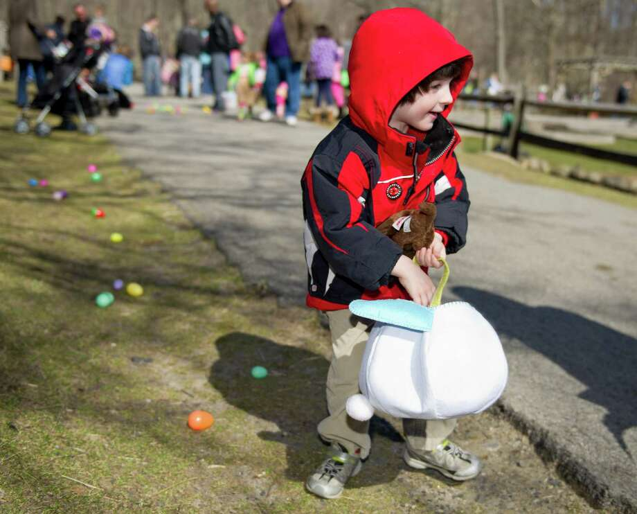 L.J. Stephens, 3, collects eggs during the 9th Annual Heckscher Farm Egg Hunt on Saturday, March 30, 2013. Photo: Lindsay Perry / Stamford Advocate