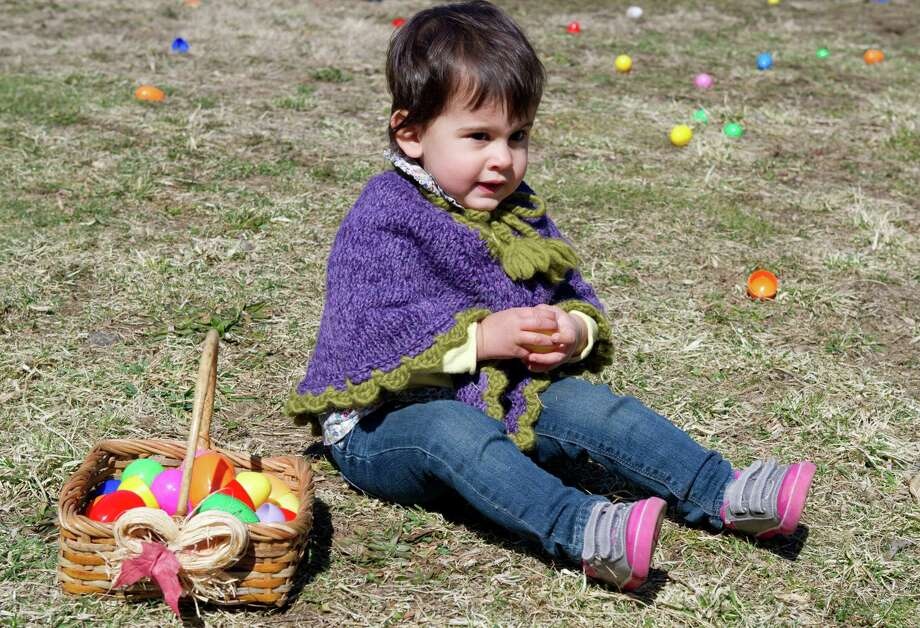 Kirsten Cook, 1, collects eggs during the 9th Annual Heckscher Farm Egg Hunt on Saturday, March 30, 2013. Photo: Lindsay Perry / Stamford Advocate