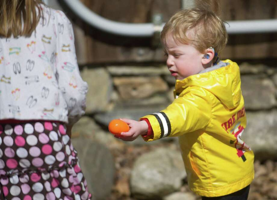 Aaron Palker, 2, gives away an egg he found during the 9th Annual Heckscher Farm Egg Hunt on Saturday, March 30, 2013. Photo: Lindsay Perry / Stamford Advocate
