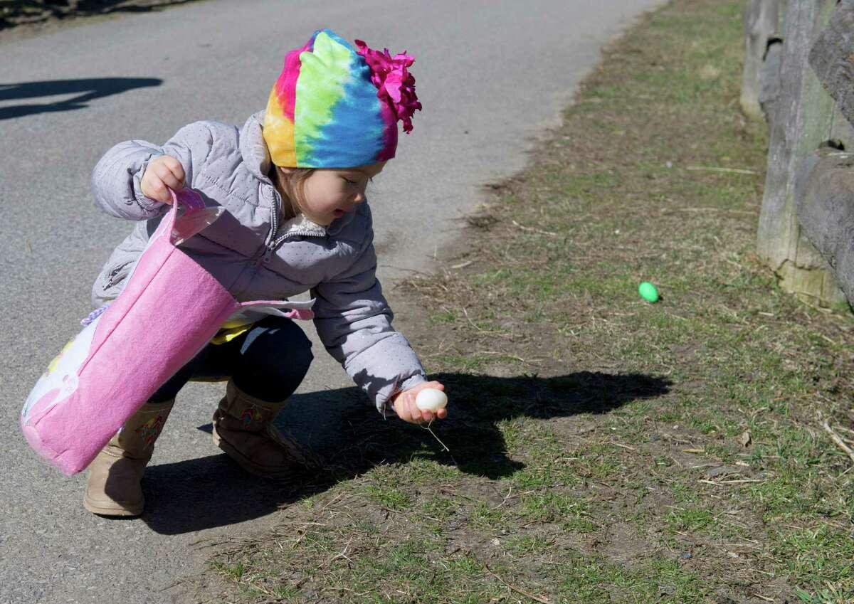 Iris Lee-Jensen, 2, picks up an egg during the 9th Annual Heckscher Farm Egg Hunt on Saturday, March 30, 2013.