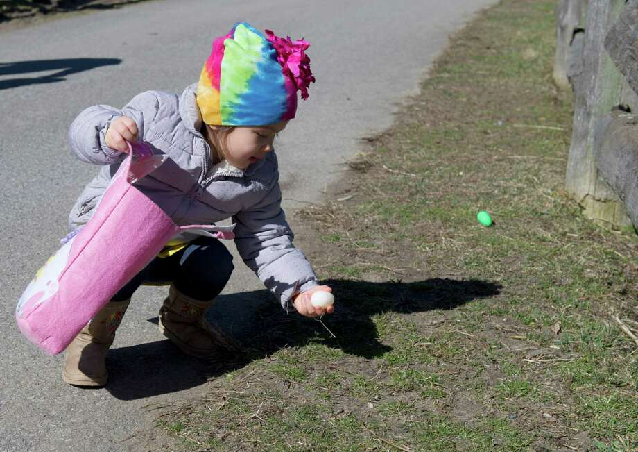 Iris Lee-Jensen, 2, picks up an egg during the 9th Annual Heckscher Farm Egg Hunt on Saturday, March 30, 2013. Photo: Lindsay Perry / Stamford Advocate