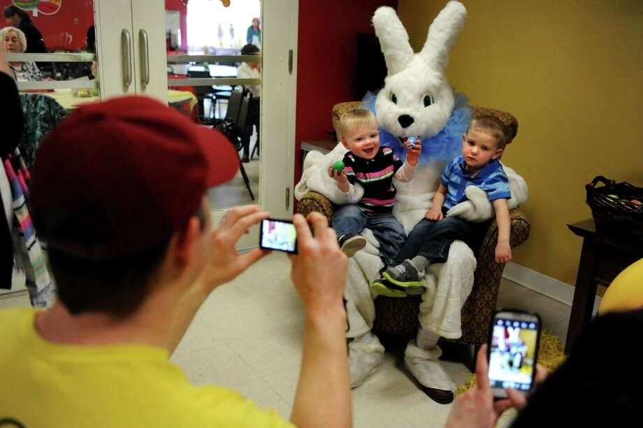 Ryan Wersted, 17 months, of Colonie, center, and Tommy D'Allaird, 3, of Clifton Park pose with the Easter Bunny at an Easter party on Saturday, March 30, 2013, at the Watervliet Senior Citizens Center in Watervliet, N.Y. Ryan's father, Ken Wersted, left, captures the moment. (Cindy Schultz / Times Union) Photo: Cindy Schultz / 00021629A