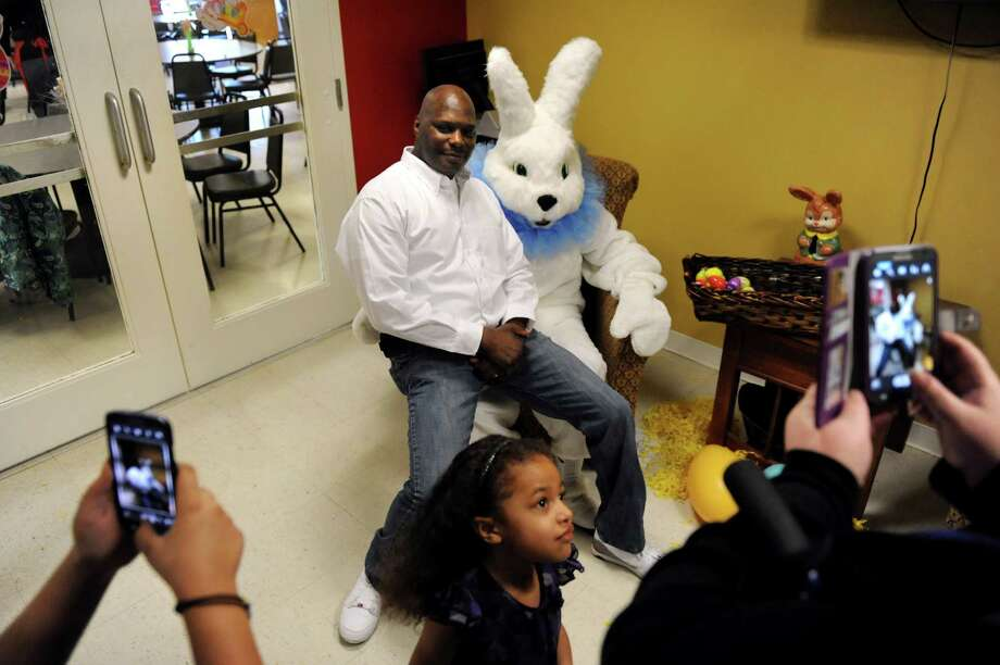 Cisco Alecia of Watervliet, center, poses with the Easter Bunny as family members take pictures on Saturday, March 30, 2013, at the Watervliet Senior Citizens Center in Watervliet, N.Y. His daughter Jaidyn Alecia, 5, center, joins them. (Cindy Schultz / Times Union) Photo: Cindy Schultz / 00021629A