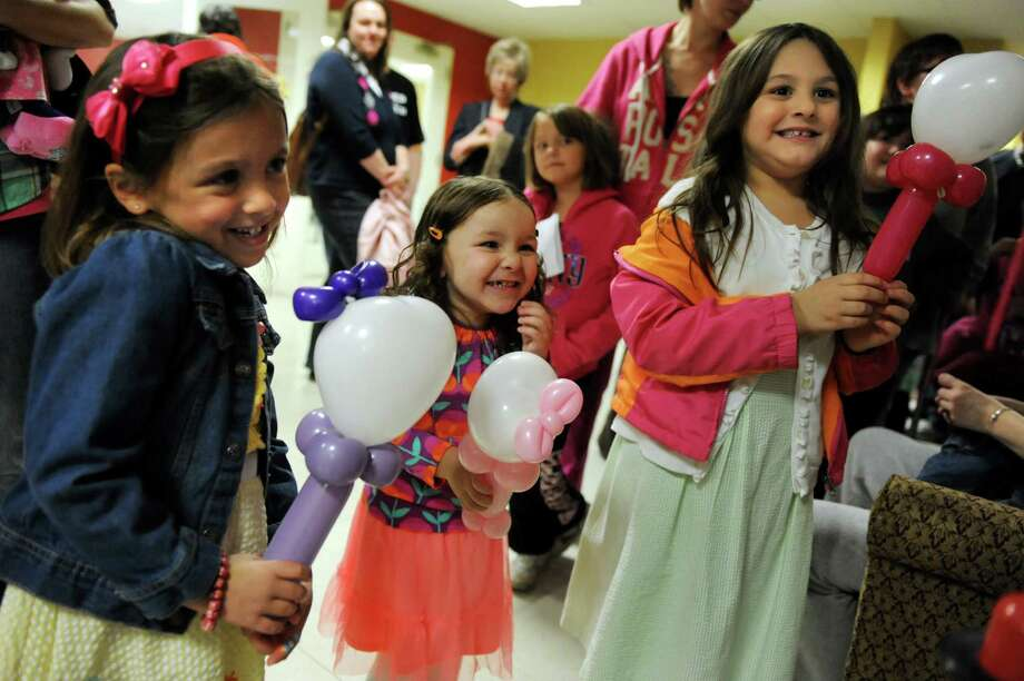 Jean Marie DiCaprio, 4, of Ballston Spa, left, her cousin Isabella Pontari, 3, of Watervliet, and sister Gianna DiCaprio, 5, get balloons in the shape of Hello Kitty at an Easter party on Saturday, March 30, 2013, at the Watervliet Senior Citizens Center in Watervliet, N.Y. (Cindy Schultz / Times Union) Photo: Cindy Schultz / 00021629A