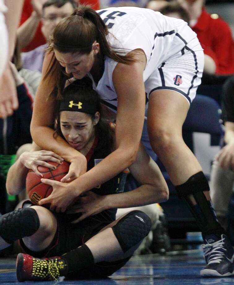 Maryland guard Chloe Pavlech, bottom, tries to keep a grip on the ball against Connecticut center Stefanie Dolson, top, during the first half of an NCAA women's college regional semifinal basketball game in Bridgeport, Conn., Saturday, March 30, 2013. (AP Photo/Charles Krupa)