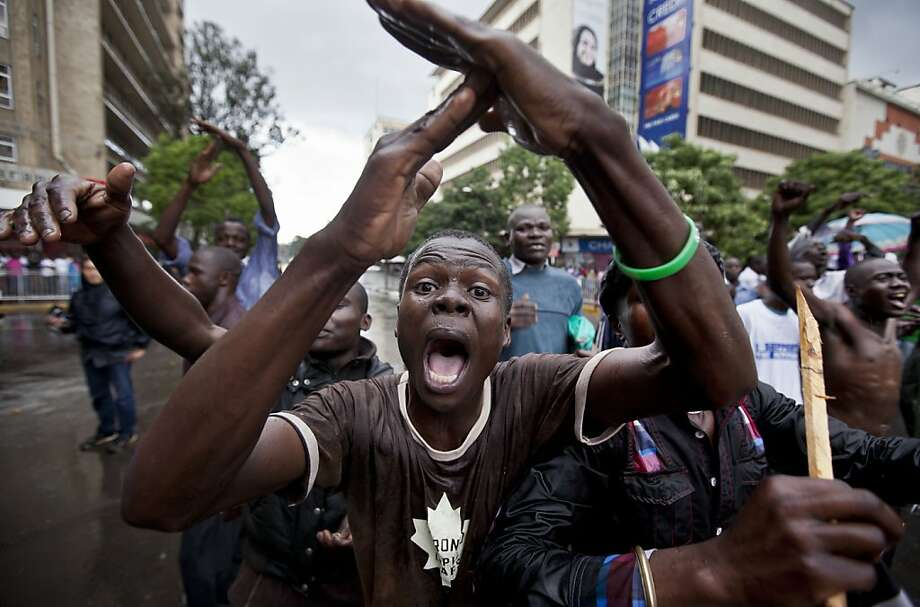 A supporter of losing presidential candidate Raila Odinga gestures as he protests with others in the rain in front of riot police guarding the Supreme Court in Nairobi, Kenya Saturday, March 30, 2013. Kenya's Supreme Court on Saturday upheld the election of Uhuru Kenyatta as the country's next president, in a verdict on a petition by candidate Raila Odinga appealing the election result, ending an election season that riveted the nation amid fears of a repeat of the 2007-08 postelection violence. (AP Photo/Ben Curtis) Photo: Ben Curtis, Associated Press