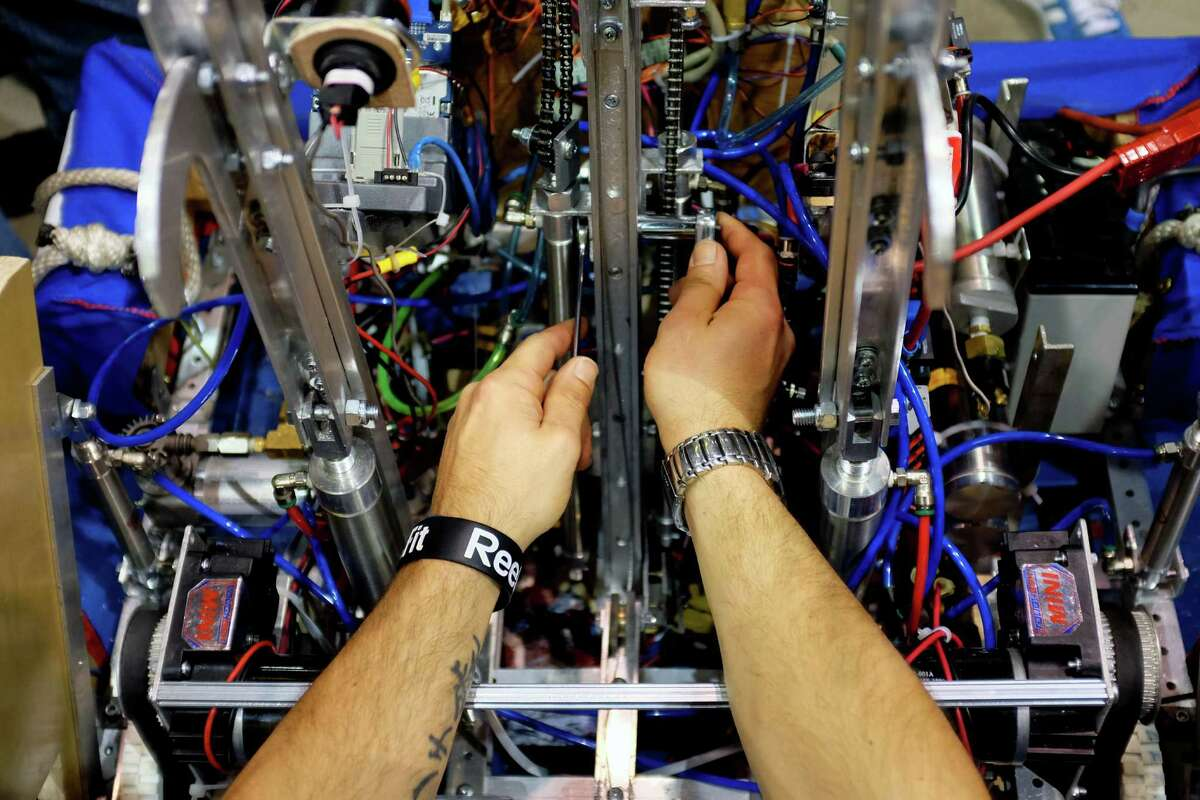 A robot is repaired in the pits during the qualifying rounds of the FIRST Robotics Competition Saturday, March 30, 2013, at the CenturyLink Field Event Center in Seattle. Sixty-four high school students competed - robot against robot - in a challenge that tested their technological creations' ability to throw Frisbees into goals.