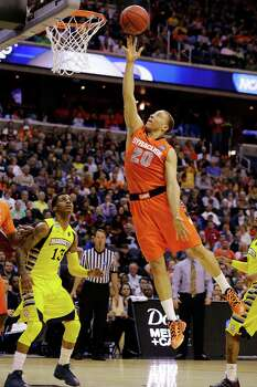 Syracuse guard Brandon Triche (20) heads towards the basket as Marquette guard Vander Blue (13) watches during the first half of the East Regional final in the NCAA men's college basketball tournament, Saturday, March 30, 2013, in Washington. (AP Photo/Alex Brandon) Photo: Alex Brandon, Associated Press / AP