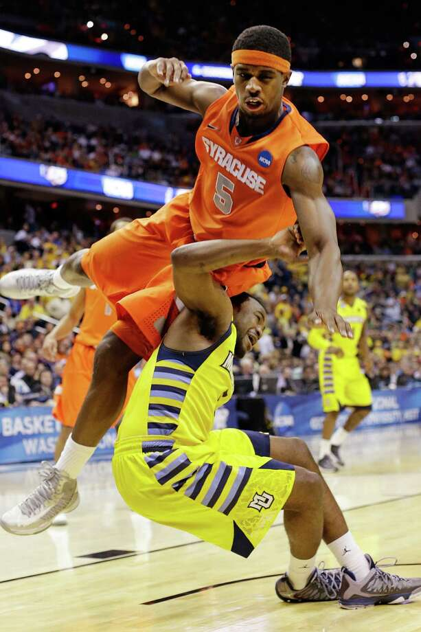 Syracuse forward C.J. Fair (5) falls on Marquette guard Junior Cadougan (5) during the first half of the East Regional final in the NCAA men's college basketball tournament, Saturday, March 30, 2013, in Washington. (AP Photo/Pablo Martinez Monsivais) Photo: Pablo Martinez Monsivais, Associated Press / AP