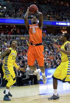 Syracuse forward C.J. Fair (5) shoots between Marquette guard Vander Blue (13) and Marquette guard Junior Cadougan (5) in the first half of the NCAA Tournament East Regional final at the Verizon Center in Washington, D.C., Saturday, March 30, 2013. (Harry E. Walker/MCT) Photo: Harry E. Walker, McClatchy-Tribune News Service / Harry E. Walker, Copyright 2012