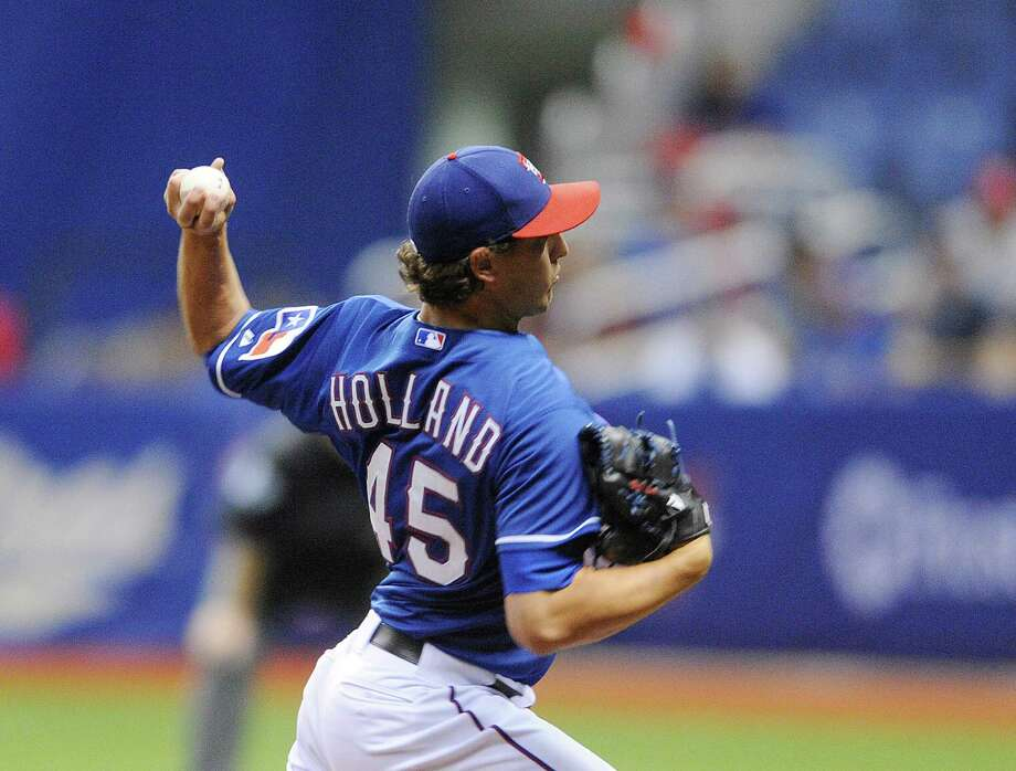 Texas Rangers pitcher Derek Holland bears down against the San Diego Padres during Big League Weekend exhibition baseball action at the Alamodome on Saturday, March 30, 2013. Photo: Billy Calzada, Express-News / San Antonio Express-News