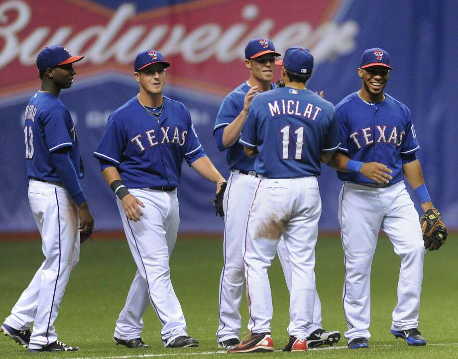 The Texas Rangers greet each other after defeating the San Diego Padres in Big League Weekend exhibition baseball action at the Alamodome on Saturday, March 30, 2013. Photo: Billy Calzada, Express-News / San Antonio Express-News