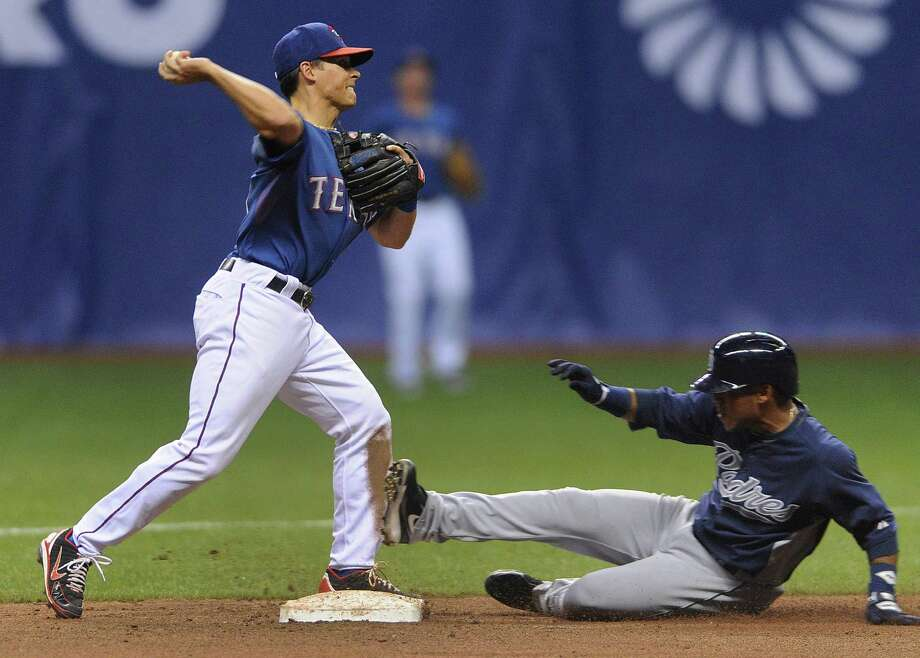 Second baseman Greg Miclat of the Texas Rangers turns a double play as Will Venable of the San Diego Padres slides in during Big League Weekend exhibition baseball action at the Alamodome on Saturday, March 30, 2013. Photo: Billy Calzada, Express-News / San Antonio Express-News