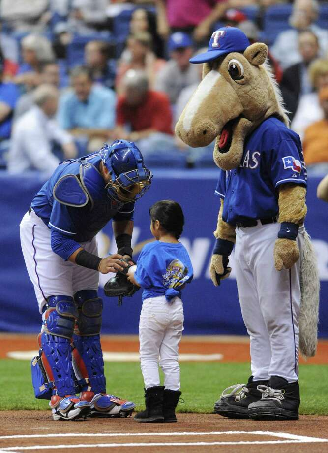 A child receives an autograph from Texas Rangers catcher Geovany Soto as Rangers Captain, the Texas Rangers mascot, stands by before the Big League Weekend exhibition baseball game between the San Diego Padres and the Rangers at the Alamodome on Saturday, March 30, 2013. Photo: Billy Calzada, Express-News / San Antonio Express-News