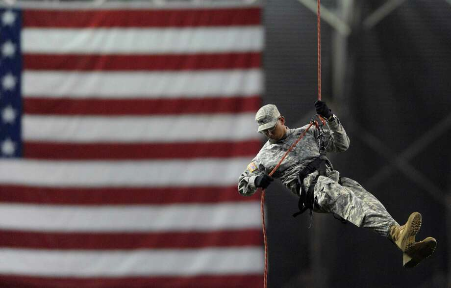 A member of the U.S. Army North Rappel Team descends with the ball for the ceremonial first pitch before the Big League Weekend exhibition baseball game between the San Diego Padres and the Texas Rangers at the Alamodome on Saturday, March 30, 2013. Photo: Billy Calzada, Express-News / San Antonio Express-News