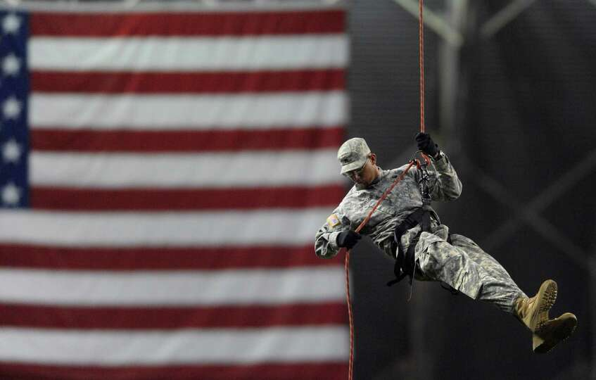 A member of the U.S. Army North Rappel Team descends with the ball for the ceremonial first pitch be