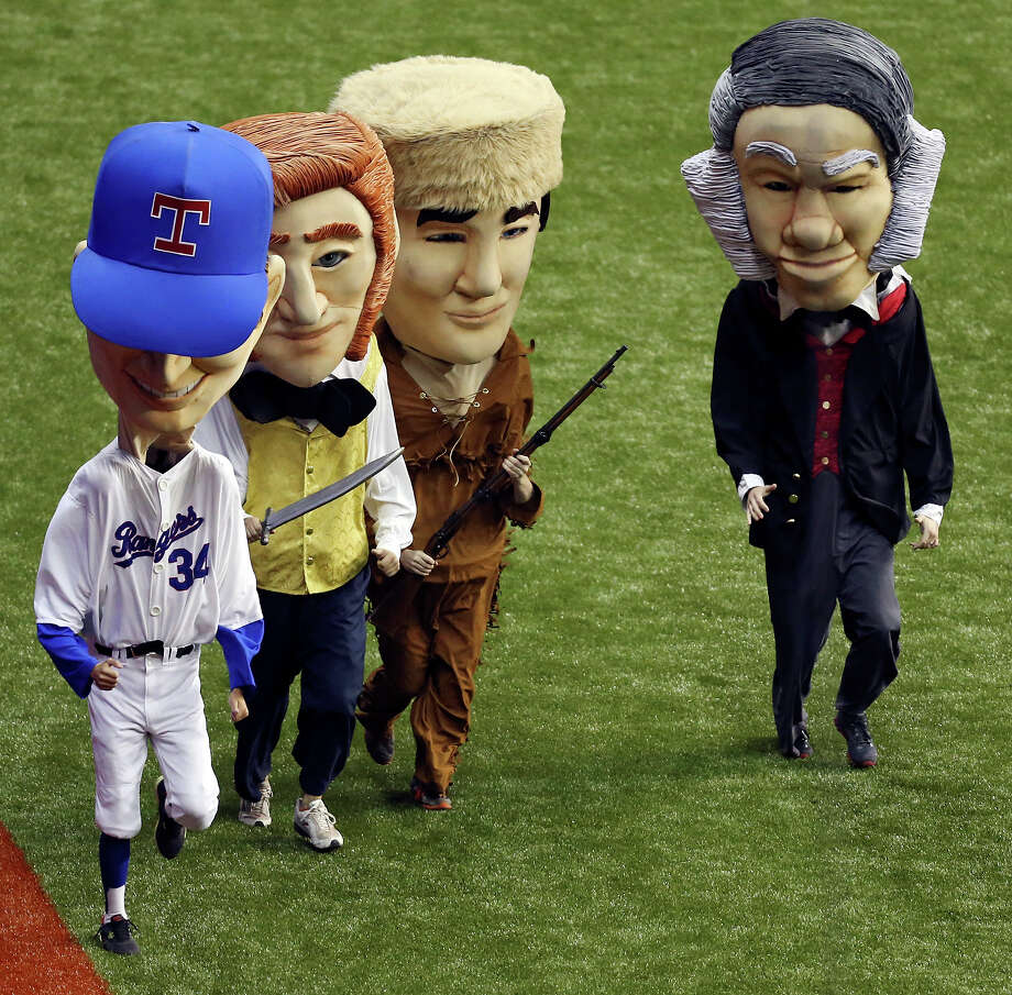 Masked characters of Nola Ryan (from left), Jim Bowie, Davy Crockett, and Sam Houston race around the field during an exhibition baseball game with the Texas Rangers and San Diego Padres part of the �Big League Weekend� Saturday March 30, 2013 at the Alamodome. The Rangers won 5-2. Photo: Edward A. Ornelas, Express-News / © 2013 San Antonio Express-News