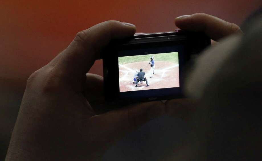A baseball fan photographs the Texas Rangers and San Diego Padres exhibition baseball game part of the �Big League Weekend� Saturday March 30, 2013 at the Alamodome. The Rangers won 5-2. Photo: Edward A. Ornelas, Express-News / © 2013 San Antonio Express-News