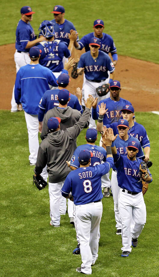 The Texas Rangers celebrate their 5-2 win over the San Diego Padres after an exhibition baseball game part of the �Big League Weekend� Saturday March 30, 2013 at the Alamodome. Photo: Edward A. Ornelas, Express-News / © 2013 San Antonio Express-News