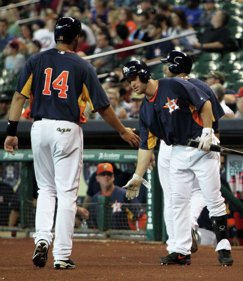 The Houston Astros left fielder J.D. Martinez left, slaps hands with teammate Trevor Crowe right, after scoring a run against the Chicago Cubs during the second inning of MLB exhibition game action at Minute Maid Park Saturday, March 30, 2013, in Houston . Photo: James Nielsen, Houston Chronicle / © 2013 Houston Chronicle